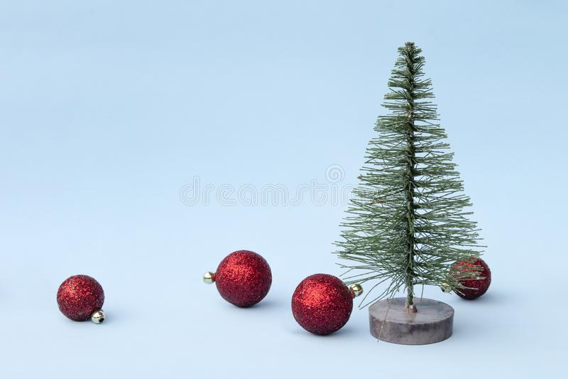 Árvore de Natal, brinquedos vermelhos no fundo azul no estilo mínimo Ornamento decorativos do Natal, ano novo e conceito do inver fotografia de stock