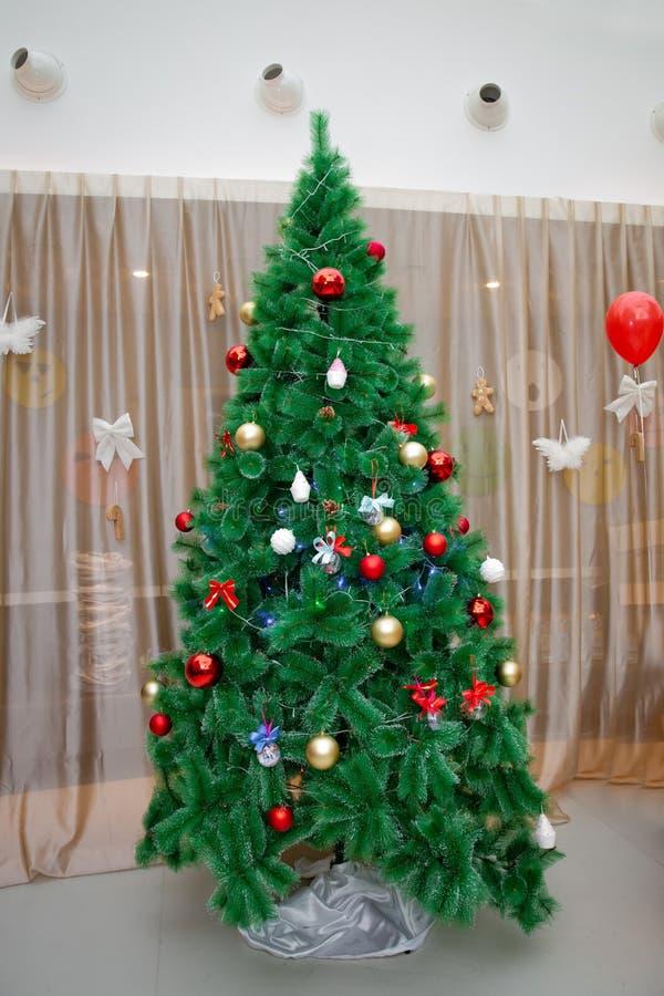 Árvore de Natal com decorações vermelhas, caixa de presente no fundo branco, sala interior do conceito do Natal Tiro alegre do es fotos de stock royalty free