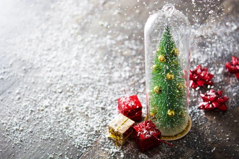 Árvore de Natal com presente da cor e neve de queda no fundo de madeira da tabela foto de stock royalty free