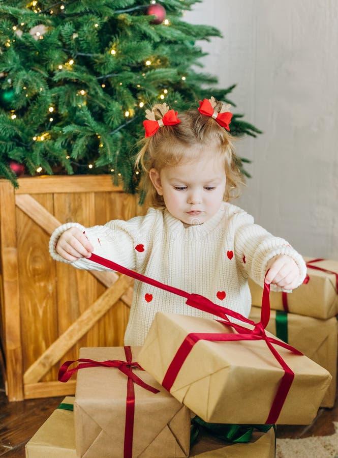 A árvore de Natal da caixa de presente da emoção da criança desata fitas fotografia de stock
