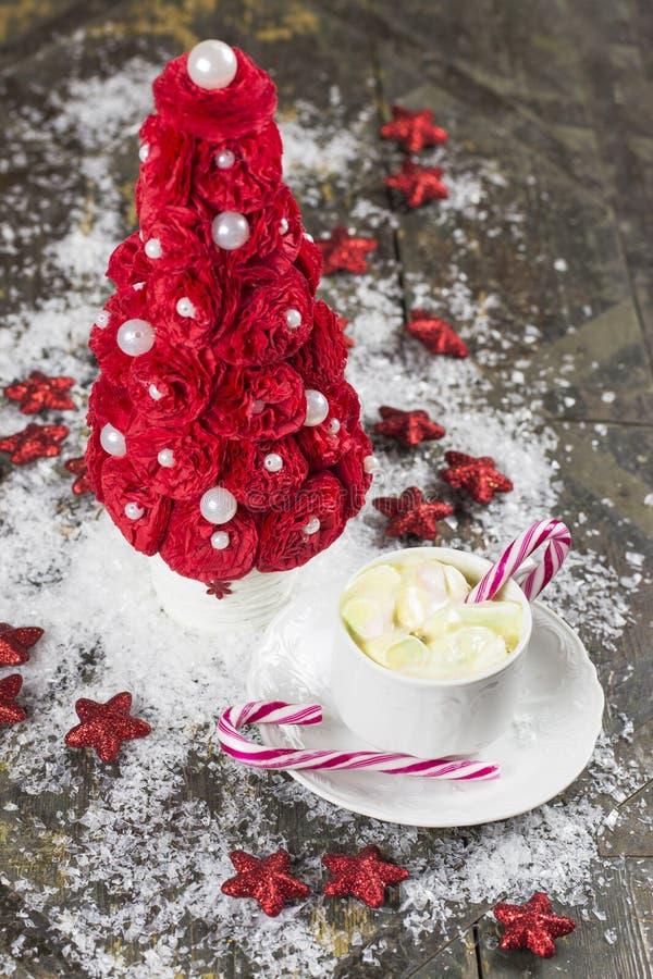 Árvore de Natal da cor vermelha cercada por estrelas e por neve em um o fotografia de stock