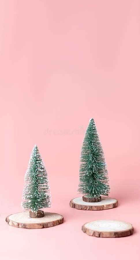 Árvore de Natal da árvore na fatia de madeira do log na parte traseira do estúdio do rosa pastel fotos de stock