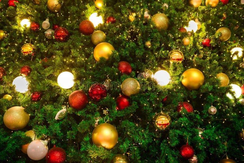 Árvore de Natal decora com bola vermelha e dourada entre a luz amarela imagens de stock