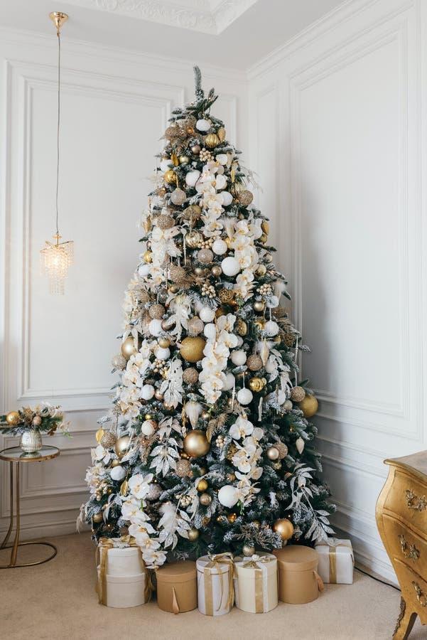 Árvore de Natal decorada com as caixas de presente na sala branca foto de stock royalty free