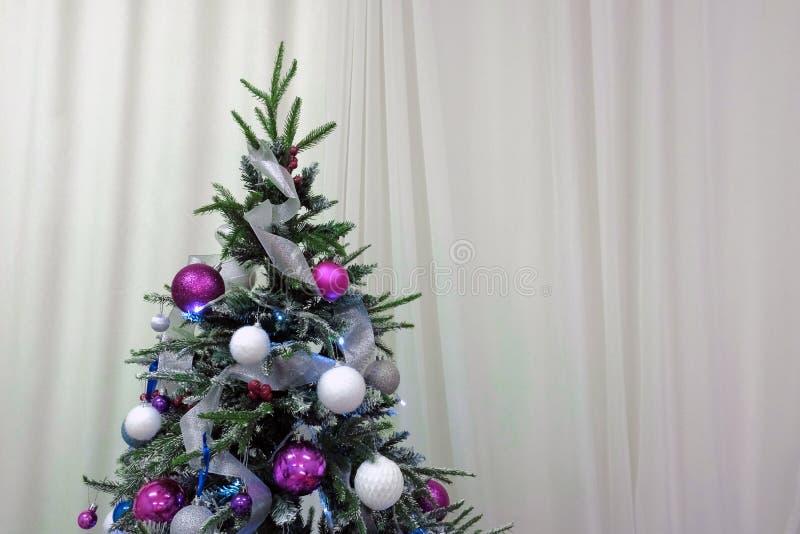 Árvore de Natal decorada com bolas e festões em um fundo das cortinas brancas Copie o espaço Decoração tradicional para comemorar imagens de stock royalty free