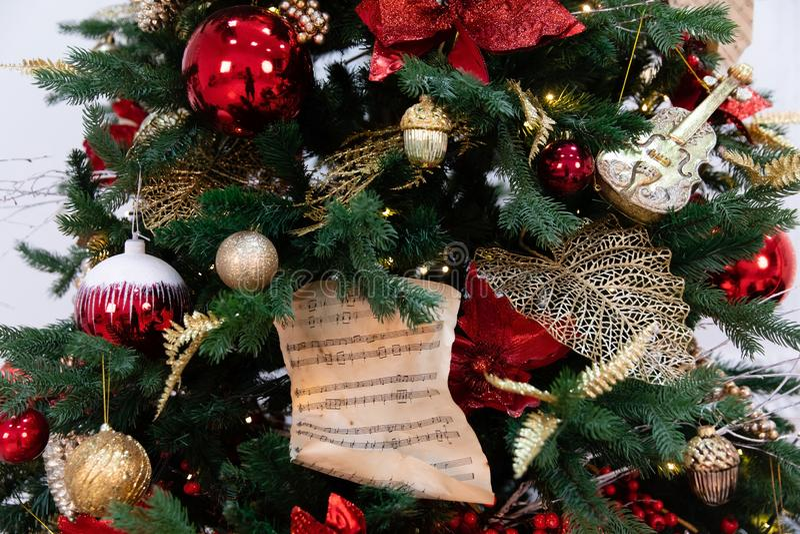 Árvore de Natal decorada com brinquedos, luzes e partitura fotos de stock royalty free