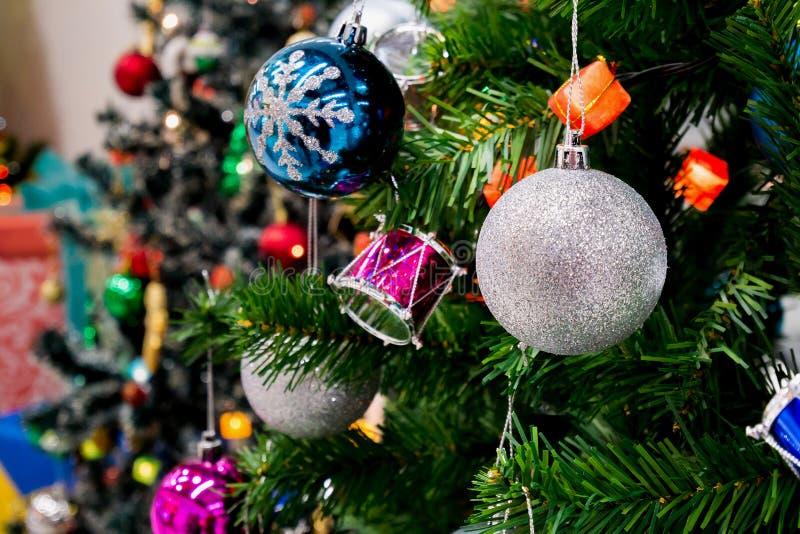 Árvore de Natal decorada com a quinquilharia colorida no bokeh efervescente imagem de stock