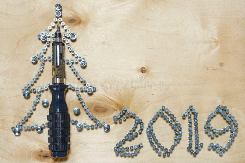 A árvore de Natal 2019 de DIY fez da chave de fenda e dos parafusos em um fundo da madeira compensada imagem de stock royalty free