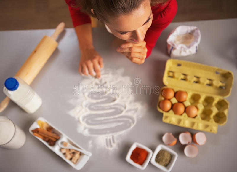 Árvore de Natal do desenho da dona de casa na mesa de cozinha com farinha imagem de stock