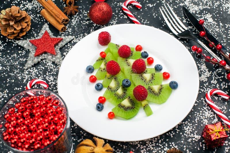Árvore de Natal do quivi com framboesa, mirtilo e airela na tabela com decoração imagem de stock