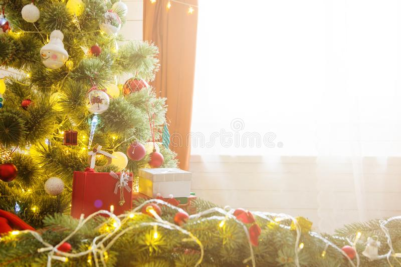 Árvore de Natal elegante com decorações e presentes no assoalho de folhosa elegante sobre a janela foto de stock