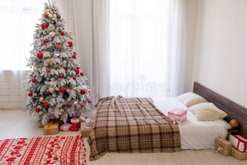 Árvore de Natal em um quarto branco com interior da cama de presentes do ano novo fotos de stock