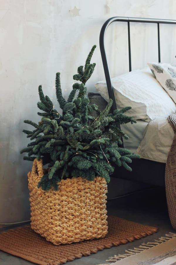 Árvore de Natal em uma cesta de vime pela cama Minimalistic Scand foto de stock royalty free