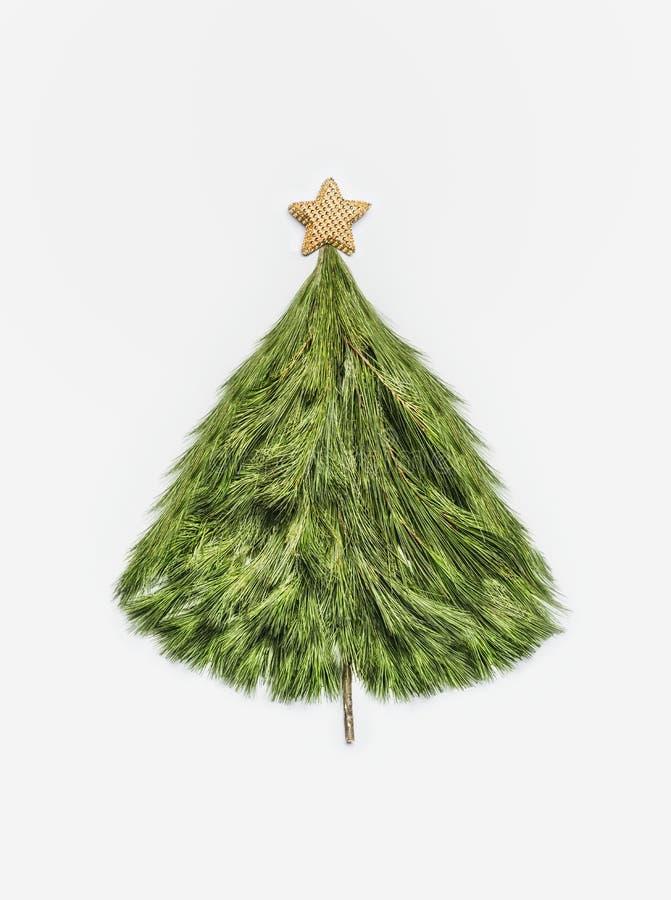 A árvore de Natal feita com cedro ramifica com a estrela do ouro no fundo branco, vista superior Disposição do cartão do feriado  imagem de stock royalty free