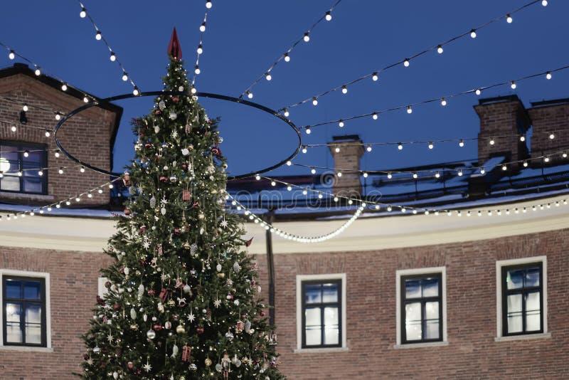 Árvore de Natal fora da parte externa nas luzes e nas festões ao lado da casa velha do tijolo imagem de stock