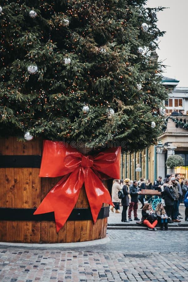 Árvore de Natal gigante em um potenciômetro com uma etiqueta do presente na frente do mercado de Covent Garden, Londres, Reino Un fotografia de stock royalty free