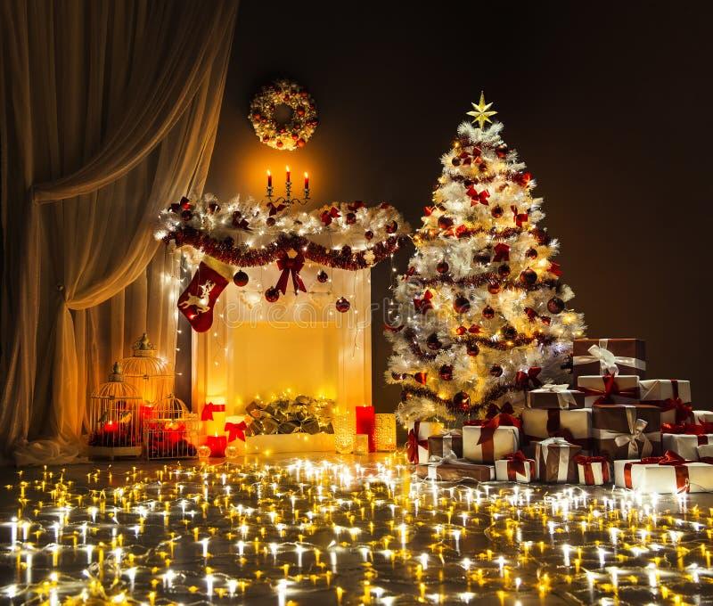 A árvore de Natal ilumina a sala interior, chaminé decorada do Xmas imagem de stock