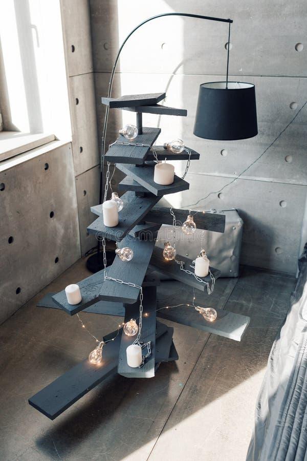 Árvore de Natal de madeira alternativa Uma árvore de Natal feito a mão e uma ampola no assoalho na sala foto de stock