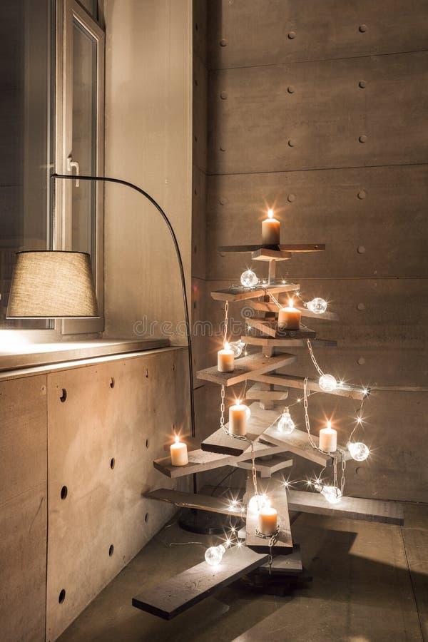 Árvore de Natal de madeira alternativa Uma árvore de Natal feito a mão e uma ampola no assoalho na sala imagem de stock royalty free