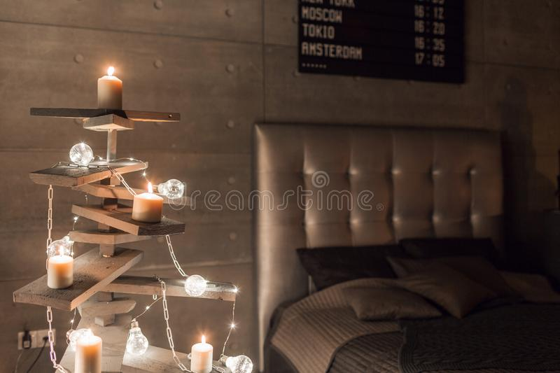 Árvore de Natal de madeira alternativa Uma árvore de Natal feito a mão e uma ampola no assoalho na sala imagem de stock