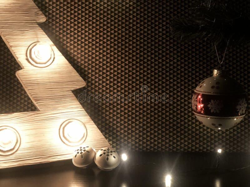Árvore de Natal de madeira com lâmpadas Brinquedos do Natal na tabela e na árvore de Natal foto de stock