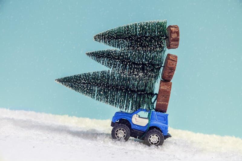 Árvore de Natal na movimentação do carro do brinquedo sobre a neve imagem de stock