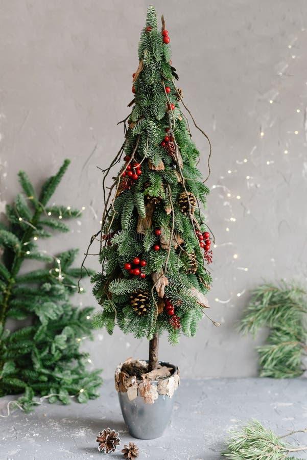 Árvore de Natal pequena decorativa com bagas vermelhas fotografia de stock royalty free