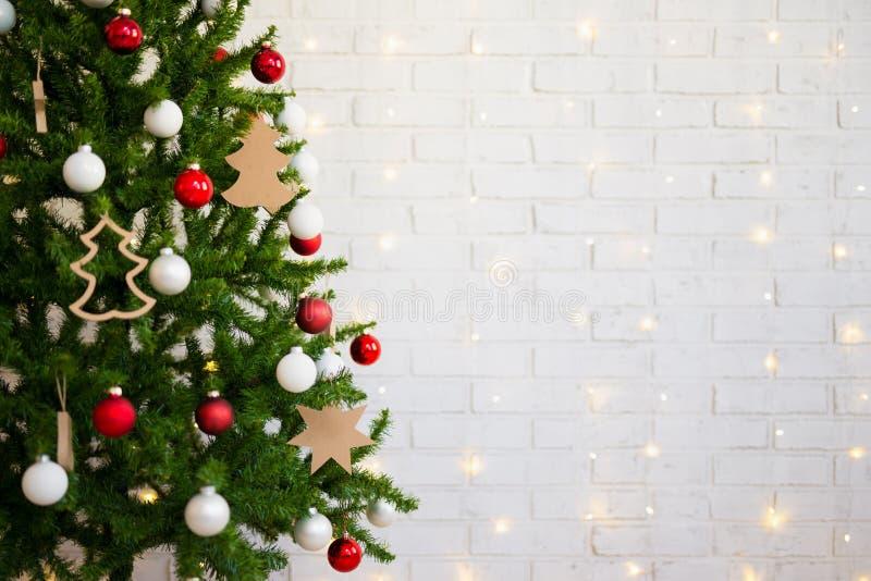 Árvore de Natal sobre a parede de tijolo branca com luzes imagens de stock