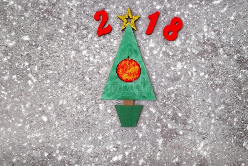 A árvore de Natal verde de madeira e assina 2018 dos redletters de madeira, fundo concreto cinzento Contexto 2018 do ano novo fel imagens de stock royalty free