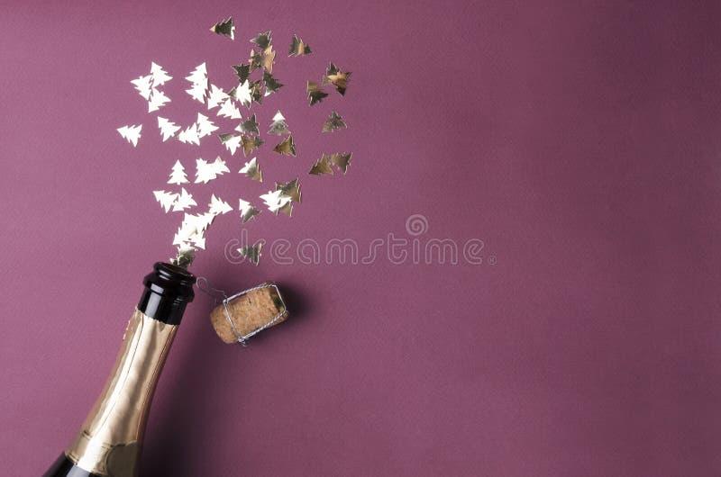 A árvore do ano novo deu forma aos confetes, garrafa de vidro do vinho na superfície violeta fotos de stock