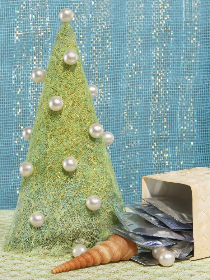 Árvore do ano novo do pano decorada com grânulos, preservativos e shell imagens de stock