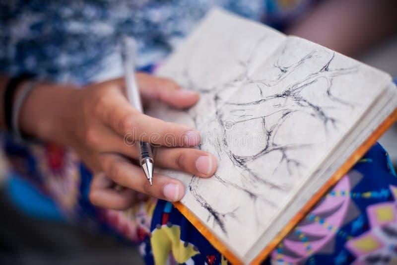 Árvore do desenho da mulher em seu caderno foto de stock