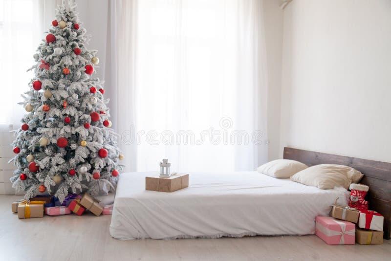 Árvore do White Christmas com a decoração vermelha dos presentes do inverno do ano novo dos brinquedos do quarto fotografia de stock royalty free