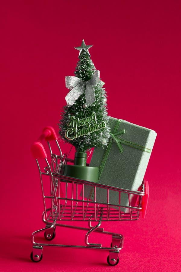 árvore e caixas de presente de Natal da quinquilharia em um carrinho de compras em um conceito cor-de-rosa do fundo, do Natal e d fotos de stock