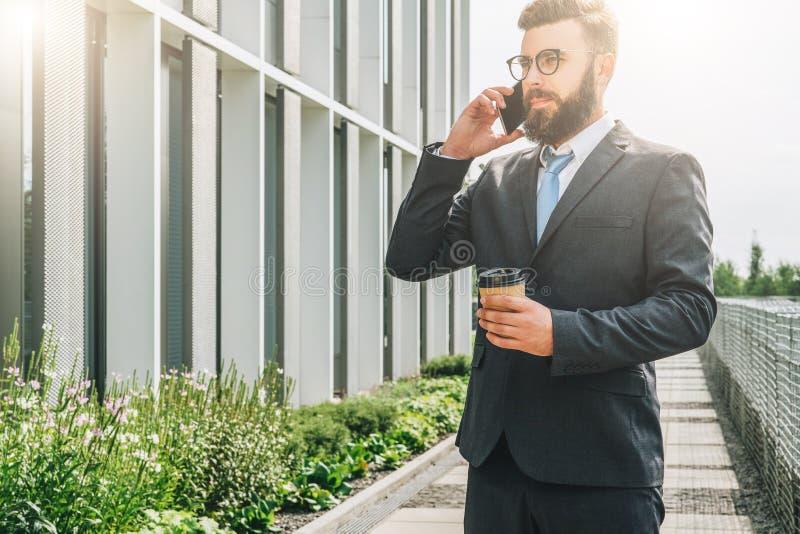 Árvore no campo Homem de negócios farpado novo no terno e laço que está café exterior, bebendo e falando no telefone celular foto de stock royalty free