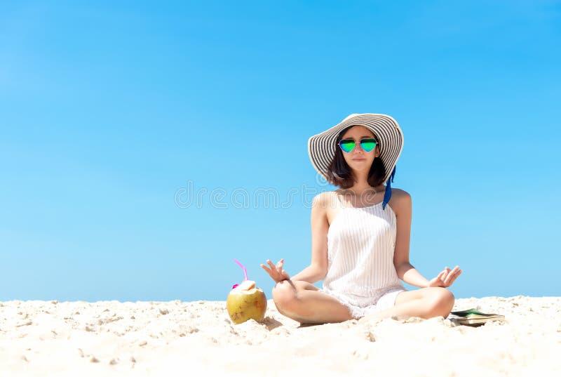 Árvore no campo Ioga asiática das mulheres do estilo de vida, relaxando e feliz na praia foto de stock