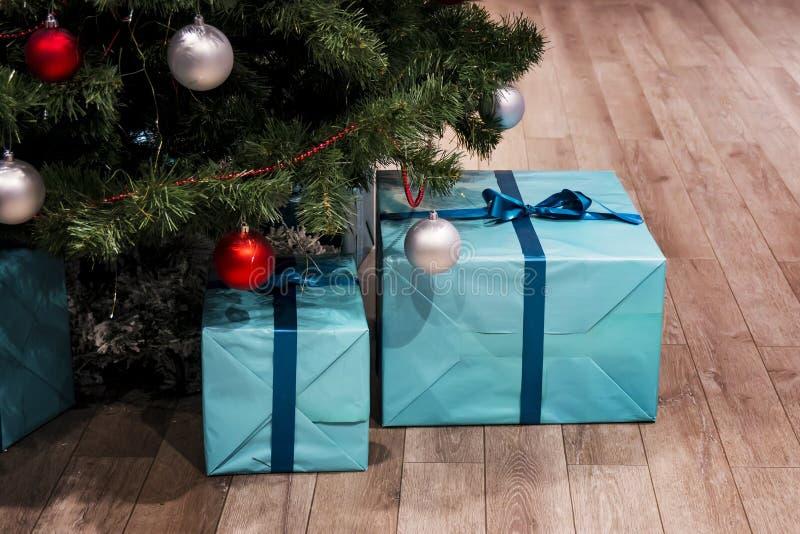 Árvore verde do Natal com decorações e presentes sob ela no interior do sótão Grandes caixas azuis em um papel de embrulho com um fotos de stock royalty free