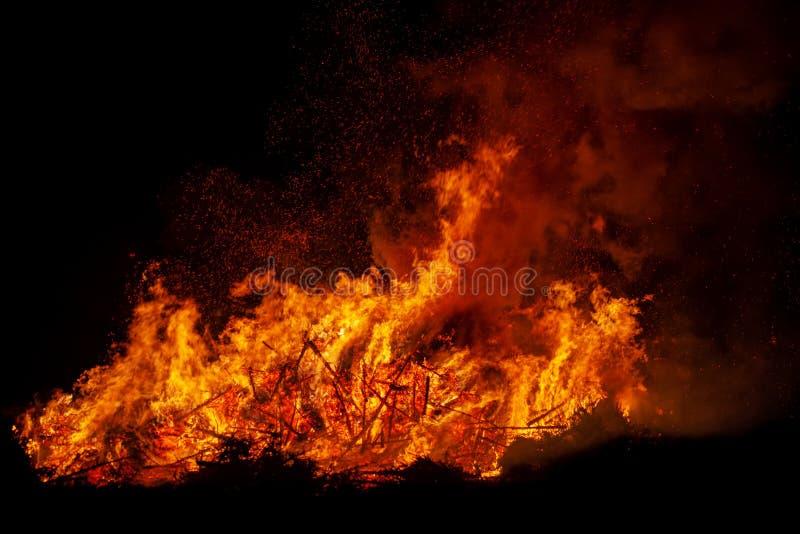 Árvores ardentes da fogueira na noite Incêndio no preto Brilhantemente, calor, luz, acampando, fogueira grande fotografia de stock