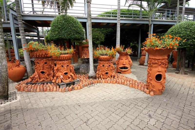 Árvores com emoções com as flor-camas no jardim botânico tropical de Nong Nooch perto da cidade de Pattaya em Tailândia foto de stock