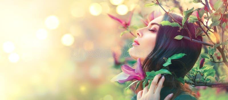 Árvores de florescência da magnólia A magnólia de toque e de cheiro da jovem mulher da beleza da mola floresce fotos de stock royalty free