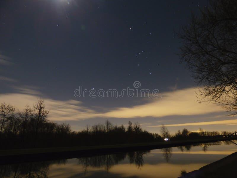 Árvores estrelados congeladas do luar do céu do canal poucas nuvens imagem de stock