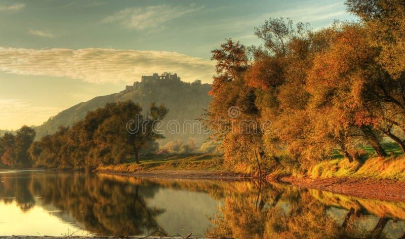 Árvores, lago e fortaleza do outono