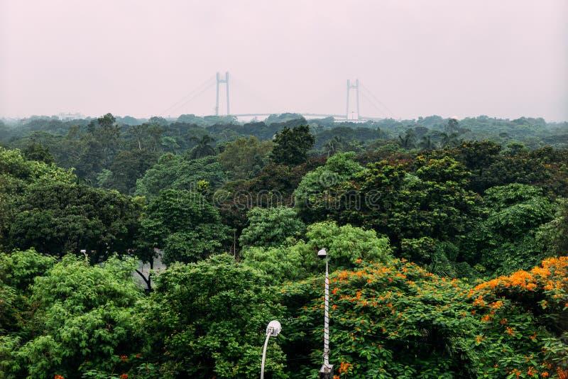 Árvores verdes e vermelhas da folha no parque de cima com de Vidyasagar Setu, igualmente conhecido como a segunda ponte de Hoogh fotografia de stock