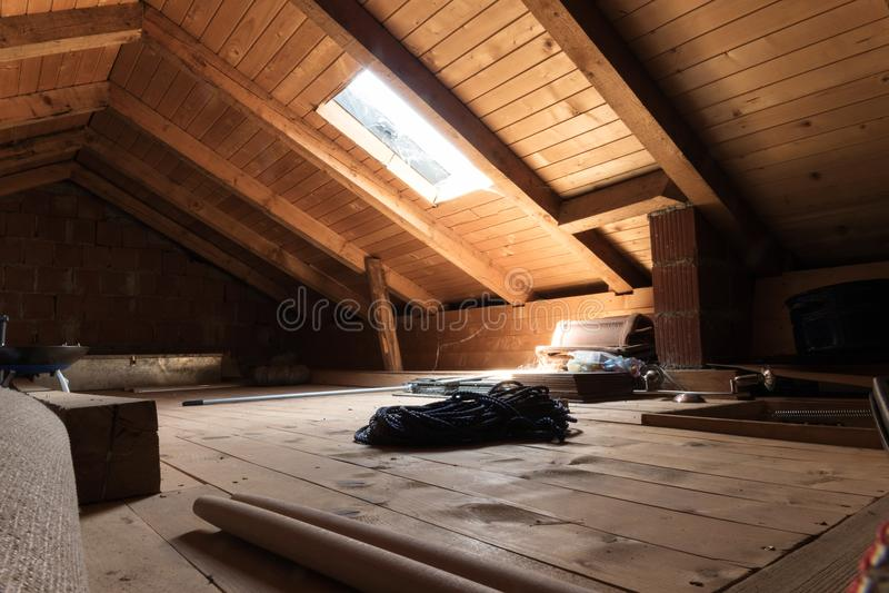 Ático de madera abandonado con la ventana diagonal del tejado imágenes de archivo libres de regalías