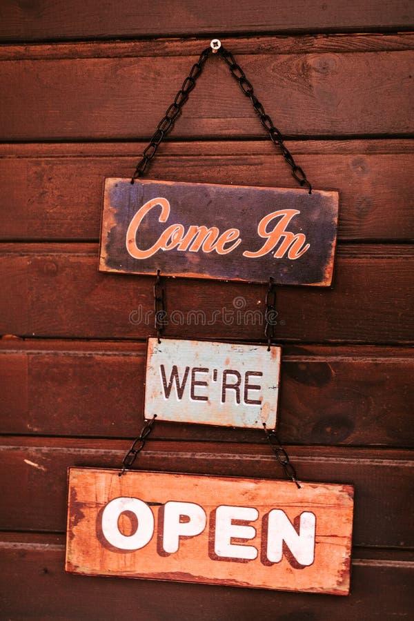 'Venga en 'muestra abierta del vintage en la pared de madera imagen de archivo