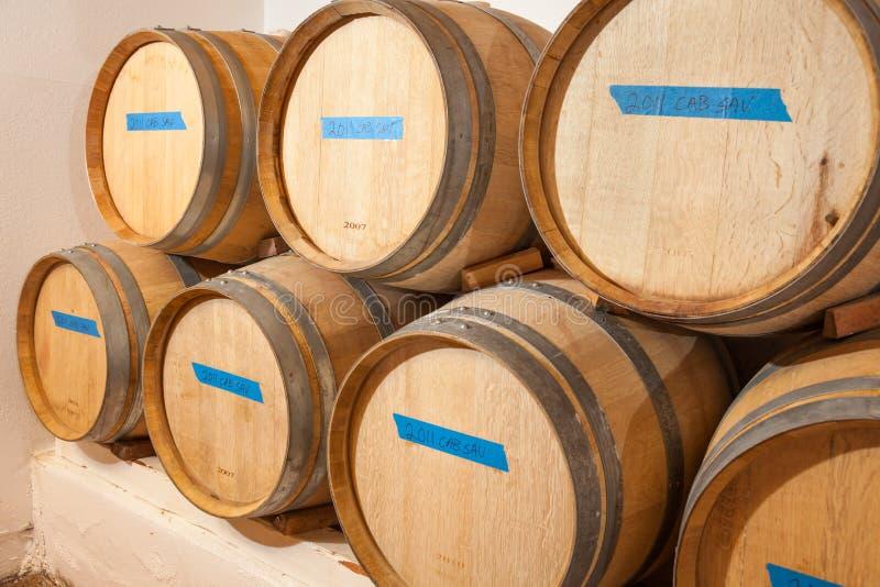 Âge de barils et de bouteilles de vin à l'intérieur de cave foncée photos stock