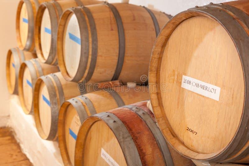 Âge de barils et de bouteilles de vin à l'intérieur de cave foncée image libre de droits