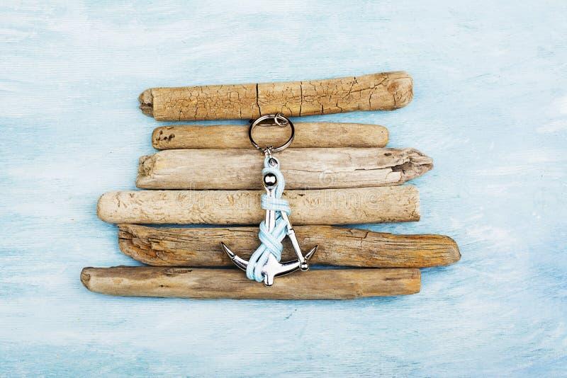 Âncora decorativa com projeto abstrato da madeira lançada à costa no fundo da areia da praia fotografia de stock