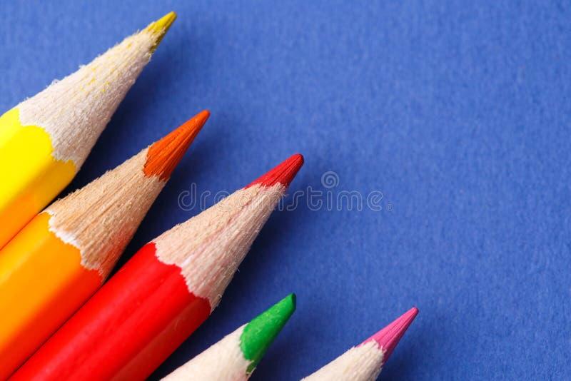 Ângulo colorido dos lápis Muitos lápis coloridos diferentes no fundo azul fotos de stock royalty free