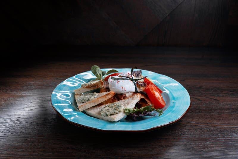 Ägg 'som tjuvjagas 'med skivor av den nya tomaten och stekt rostat bröd med läcker pate och gräsplaner på en blå platta i en orie arkivfoton